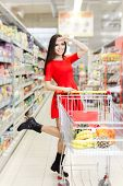 image of local shop  - Portrait of a young girl in a market store with a shopping cart - JPG