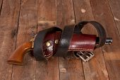 pic of revolver  - A revolver in a holster on a wooden background - JPG