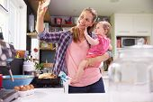 image of two women taking cell phone  - Mother Taking Selfie On Mobile Phone Holding Young Daughter - JPG