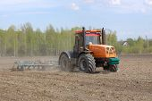 foto of plowed field  - Tractor with a cultivator plowing the field in the spring - JPG