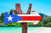 stock photo of greater antilles  - Puerto Rico Flag wooden sign with beach background - JPG