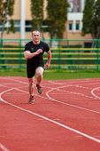 stock photo of race track  - healthy man run on athletics race sport track and representing concept of sport and speed - JPG