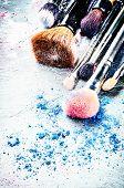 pic of bristle brush  - Makeup brushes and crushed eyeshadow on dark background - JPG