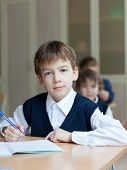 stock photo of diligent  - Diligent preschools sitting at desk in classroom - JPG