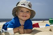 stock photo of beach hat  - small boy smiling on the beach with hat and beach toys - JPG