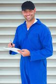 foto of overalls  - Handyman in blue overall writing on clipboard against grey shutters - JPG