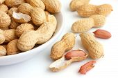 stock photo of ceramic bowl  - Round ceramic bowl of peanuts in shells - JPG