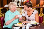 image of granddaughter  - Senior woman and granddaughter drinking coffee and eating cake in cafe - JPG