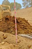 stock photo of bulldozer  - A large bulldozer spreads dirt and rock for a new fill layer on a commercial construciton road project - JPG