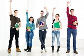 stock photo of fist  - Group of cheerful students with book - JPG