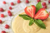 foto of custard  - Custard dessert with fresh strawberry and mint on a light background with berries