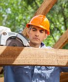 picture of sawing  - Male construction worker using electric saw on timber frame at site - JPG