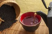stock photo of black tea  - on bamboo Mat cast iron kettle and a Cup of hot tea spilled black tea - JPG