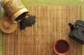 pic of black tea  - on bamboo Mat cast iron kettle and a Cup of hot tea spilled black tea - JPG