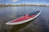 foto of paddling  - red SUP paddleboard with a paddle on a lake shore ready for paddling - JPG