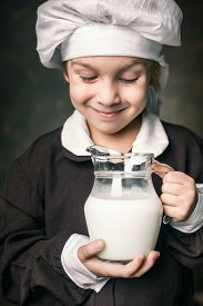 stock photo of milkman  - milkman boy holding a glass of milk - JPG