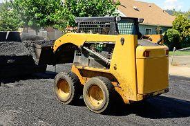 foto of skid-steer  - Small skid steer tractor moving asphalt on a repaving project - JPG