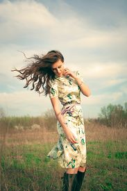 stock photo of hair motion  - young woman in summer dress in grass field - JPG