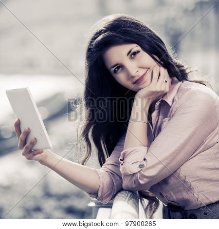 Young woman using a digital tablet computer outdoor
