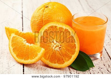 Orange fruit and glass of juice on ooden background