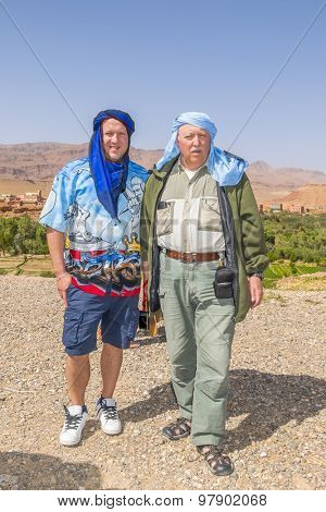TINERHIR, MOROCCO, APRIL 11, 2015: Tourists (father and son) pose for photo in berber blue turban with Tinerhir - town near Todgha Gorge in background