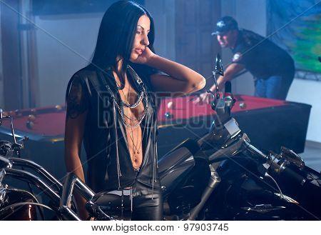 woman posing near motorbikes man playing billiards