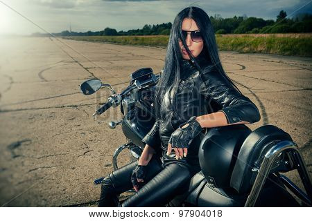 Biker girl in leather jacket sitting on a motorcycle.