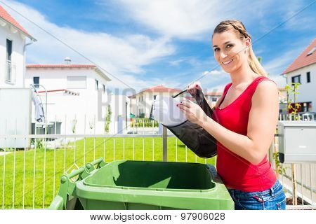 Woman emtying trash or garbage into litter box