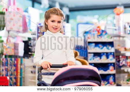 Little girl playing with baby doll carriage in toy store