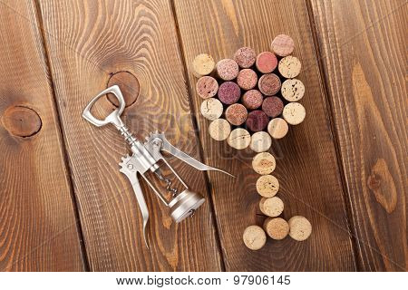 Glass shaped corks and corkscrew. View from above over rustic wooden table background