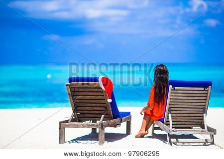 Christmas concept: beach loungers with red Santa Hat and beautiful girl during tropical vacation