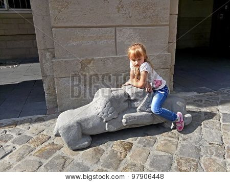 Small Girl Sitting On The Lions Sculpture