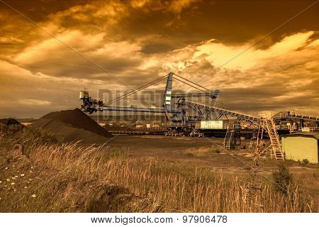 A giant wheel excavator in brown coal mine at sunset