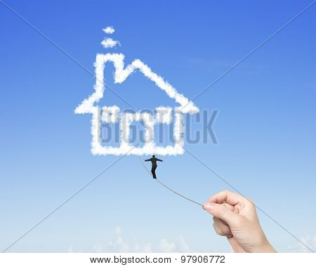 Businessman Walking Tightrope Woman Hand Pulling Toward House Clouds