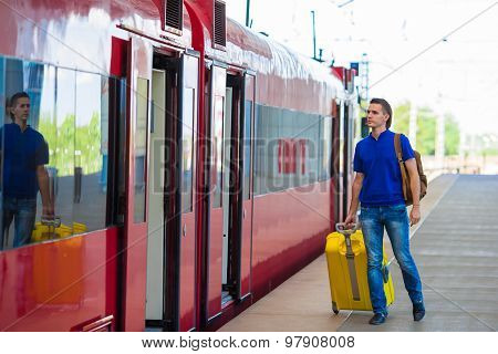 Young caucasian man with luggage at station traveling by train