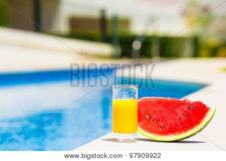 Summer and fresh theme: red ripe slice watermelon and glass of orange juice near pool