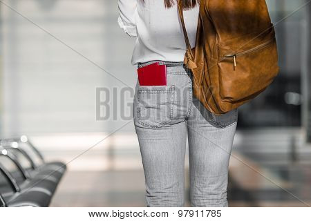 Happy young woman with air ticket and passports at airport waiting for boarding