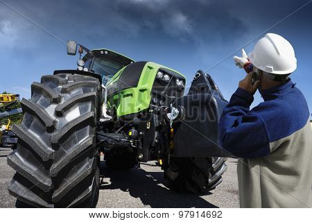 farmer, mechanic pointing at his farming tractor, latest model