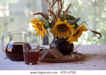 Still-life With A Bouquet Of Sunflowers And Kvass (kvas) In A Transparent Jug