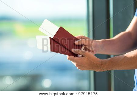Closeup passports and boarding pass at airport indoor background airplane