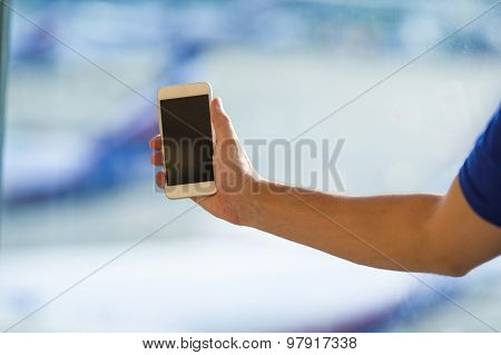 Closeup of young man use smart phone in airport background window