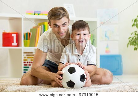child boy with dad play foot ball at home