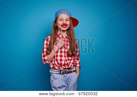 Cute girl holding red lips on stick by her mouth