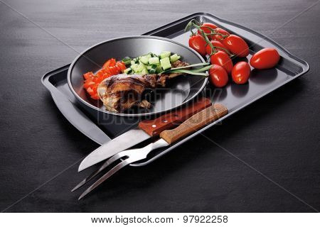fresh hot grilled turkey drumstick leg with vegetables on black metal plate over wooden table