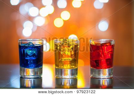 Berry alcoholic drink into small glasses on bar desk with magic illumination bokeh background