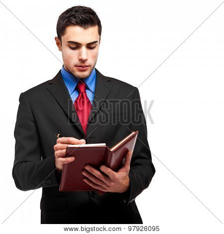 Young businessman writing on his agenda isolated on white