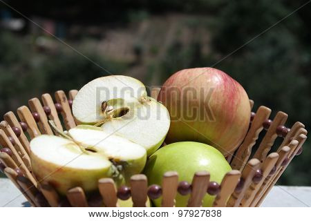 natural juicy green and red apples in wooden basket on the nature