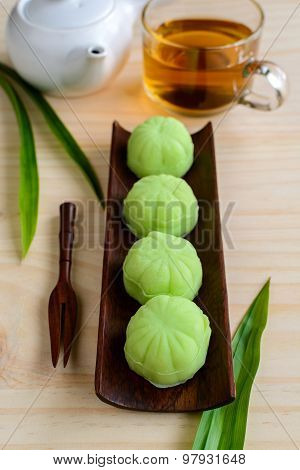 Green tea Mochi Flavored With Bean Filling And Cup Of Tea On Wooden Table