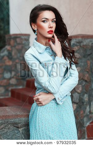 Beautiful Pretty Woman In A Denim Jacket And Turquoise Dress Near Stone