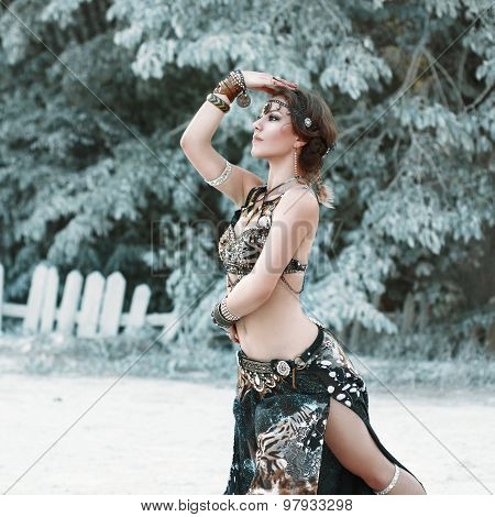 Pretty Woman Dancing In The Tribal Style On The Background Of Fabulous Trees.